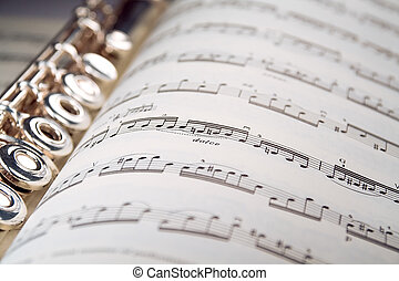 A used flute lies along the spine of an open musical score. Only one line of music is in focus.