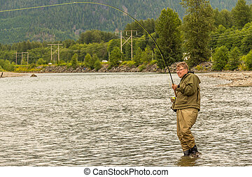 A fly fisherman hooked into a salmon on the Kitimat River, in British Columbia