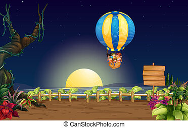A flying hot air balloon in the middle of the night