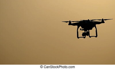 A flying quadracopter outdoors at sunset in slo-mo