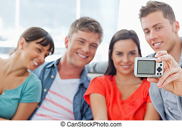 A focused shot on the camera as a group use it to take a photo of themselves