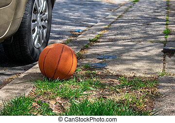 A Forgotten Basketball Next to a Car on a Suburban Street