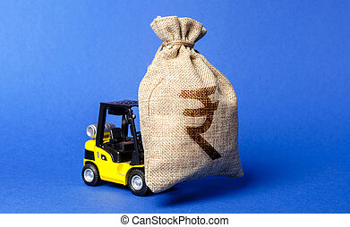 A forklift carries a huge money bag with the symbol of the Indian rupee. Budget and corruption, investment and economic growth. capital migration. Revenue profit. Superprofits, effective funds use