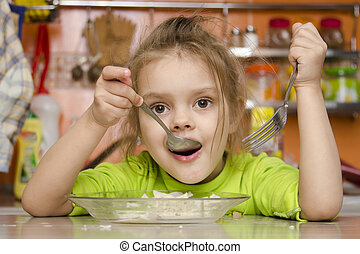 A four year old girl eats with a fo