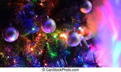 fragment of a Christmas tree with toys and lighting - A...