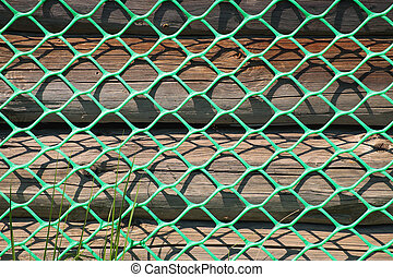 A fragment of a wooden wall with a grid