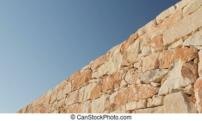 A fragment of a yellow stone wall on a blue sky background.