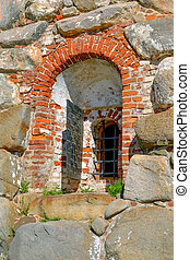 A fragment of the old wall with window and bars