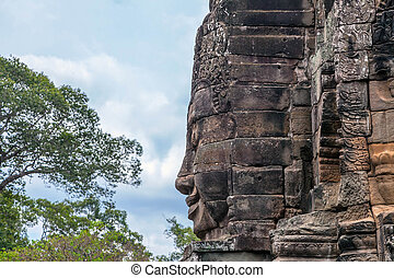 A fragment of the towers of Angkor Thom temple with image of Buddha