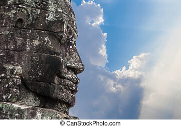 A fragment of the towers of the temple of Angkor Thom with the image of the Buddha