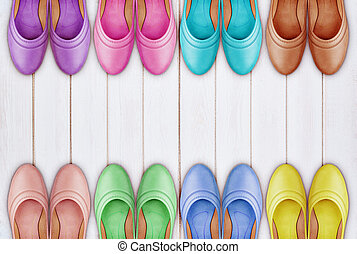 a frame of colorful leather shoes on white wooden background