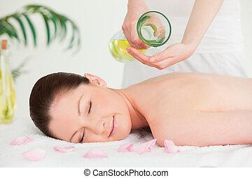 a, frau, augen schlossen, erhalten von massage, oel, auf, sie, zurück, in, a, spa