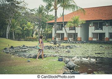 a, frau, in, pareo, futtern, grau, rückstand, gänse, und, gänschen, auf, der, see, nah, luxushotel, in, nusa, dua, trauminsel, von, bali, indonesia.