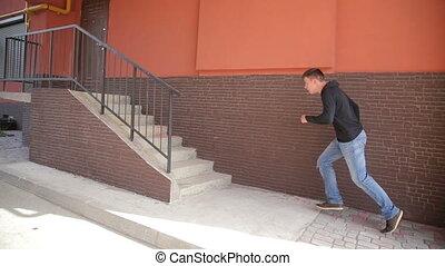 A free runner man vaults over a hand rail front flips down a...