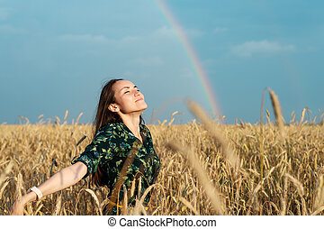 A free woman on a wheat field with her hands open breathes air against the background of a rainbow, freedom, ecology
