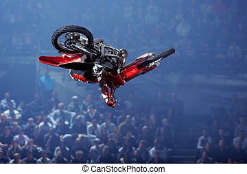 A freestyle moto cross rider performs a trick (whip) during an indoor competition with a big crowd watching