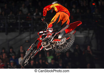 A freestyle moto-x rider goes through a trick during an indoor competition.
