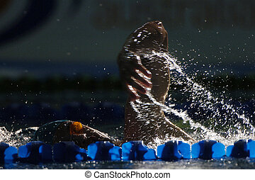 A freestyle swimmer is light up while swimming down the lap lane.
