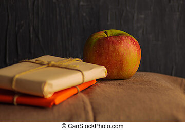 A fresh and ripe small apple rests on a kitchen towel with parcels