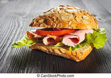 A fresh deli sandwich with ham, radish, tomatoes