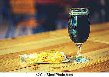A fresh glass of cold dark beer and potato chips on the wooden bar counter in pub with free space for your text. Beautiful background of the Oktoberfest.