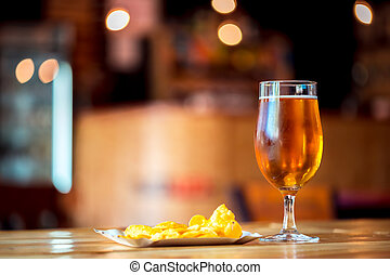 A fresh glass of cold light beer and potato chips on the wooden bar counter in pub with free space for your text. Beautiful background of the Oktoberfest.