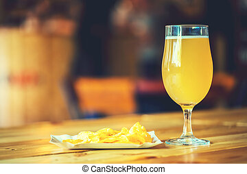 A fresh glass of cold white unfiltered beer and potato chips on the wooden bar counter in pub with free space for your text. Beautiful background of the Oktoberfest.