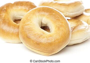A fresh plain bagel against a white background