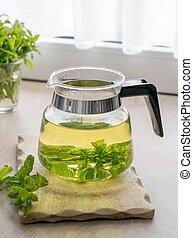 A freshly brewed glass pot of herbal mint tea