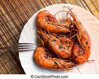 A fried lobster on a white plate, a straw lining under plate, fork, garlic, close up