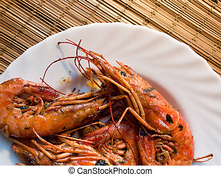 A fried lobster on a white plate, a straw lining under plate, garlic, close up