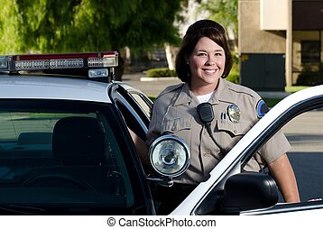 a friendly looking police officer smiles and stands next to her patrol car.