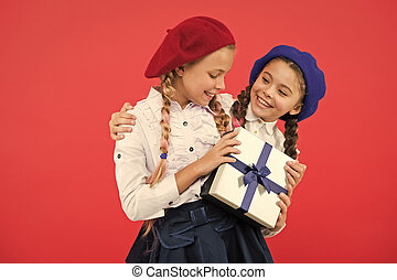 A friendship present. Little girl giving present to her friend. Happy children with small gift box wrapped with ribbon bow. Small kids enjoying holiday celebration. Birthday surprise. Happy birthday