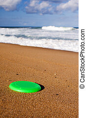 A frisbee on the beach sand - A bright green frisbee lying...
