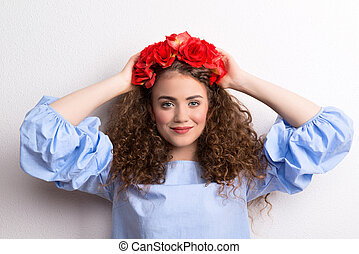 A front view of young beautiful woman with flower headband, hands behind head.