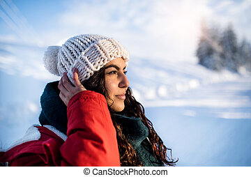 A front view portrait of young woman standing outdoors in snowy winter forest.