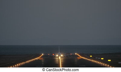A frontal takeoff at night - we see an illuminated airstrip and a blinking plane, riding to the camera and finally taking off