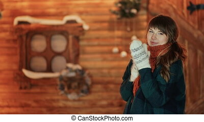 A frozen girl in mittens warms herself on the background of a wooden fairy-tale house. Christmas and New Year theme.