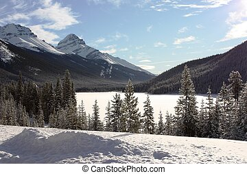 a frozen lake in front of a mountain in the rockies under blue s