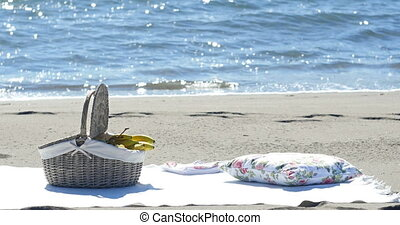 a fruit basket and a blanket for a picnic on the sandy beach