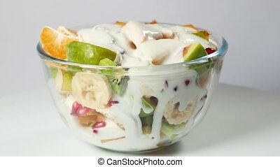 A fruit salad with mandarin, oranges, kiwi, pomegranate seeds, figs, banana and peaches