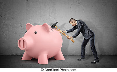 A frustrated businessman breaks his large hammer on a large solid piggy bank.