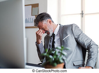 A frustrated businessman sitting at the desk in an office, hearing bad news.