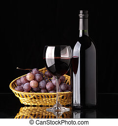 A full bottle of red wine, a glass of wine and black grapes in a wicker basket on a black background