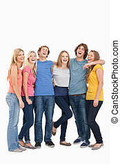 A full length shot of a group of friends laughing together and looking at the camera