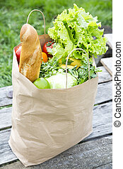 A full paper bag of healthy products stands on the wooden table.