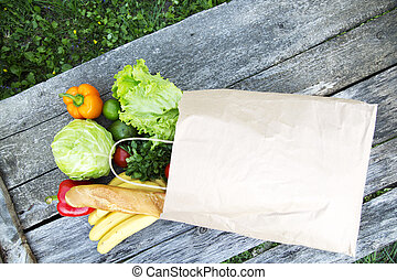 A full paper bag of healthy products stands on wooden table.