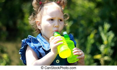 A funny beautiful child in the park smiles and drinks a...