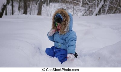 a funny child plays in the snow