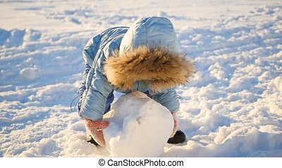 a funny child plays in the snow. child sculpts a snowball